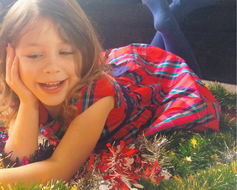 A photograph of a pretty little girl wearing a red tartan party dress from JoJo Maman Bébé and lying on her tummy in some tinsel - Christmas outfits from JoJo Maman Bébé- Mrs H's favourite things