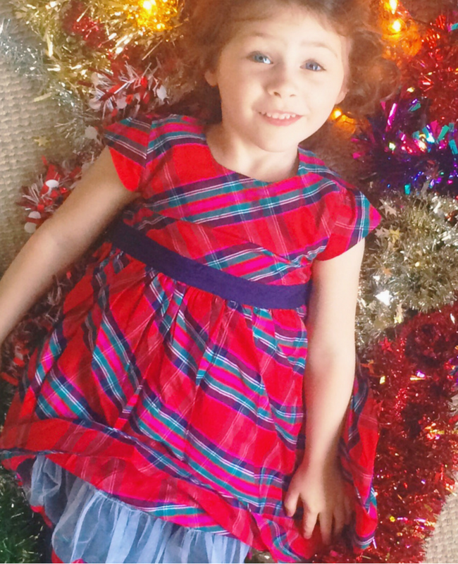 A beautiful little girl wearing a red tartan party dress from JoJo Maman Bébé lying on a bed of tinsel and fairy lights - her dress is riding up so that you can just see the netting trim underneath the skirt - Christmas outfits from JoJo Maman Bébé - Mrs H's favourite things