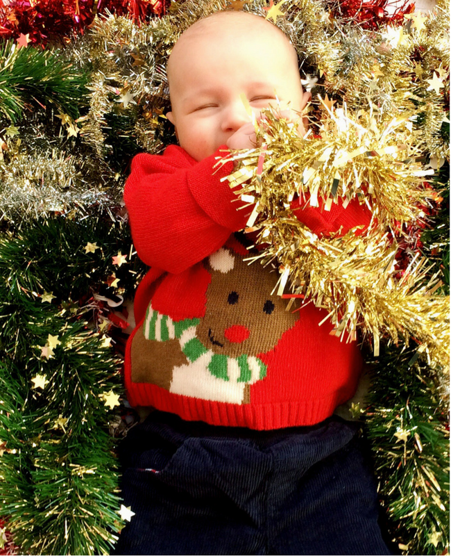 A photograph of a cute baby boy lying on a bed of tinsel and wearing a red cashmere mix reindeer Christmas jumper from JoJo Maman Bébé -Christmas outfits from JoJo Maman Bébé - Mrs H's favourite things