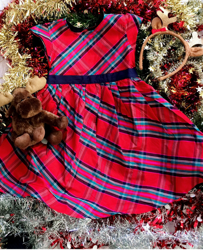 A beautiful red tartan party dress from JoJo Maman Bébé lying on a bed of tinsel with a reindeer antler head band and reindeer soft toy - Christmas outfits from JoJo Maman Bébé - Mrs H's favourite things