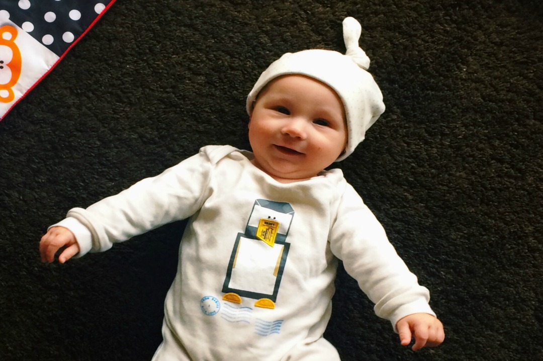 A photograph of a very cute baby boy wearing a gorgeous Penguin Baby Grow and a French Grey Little Kisses Knotted Hat from From Babies with Love AW16 Capsule Collection of organic baby clothing - Organic baby clothes review - From Babies with Love - Mrs H's Favourite Things