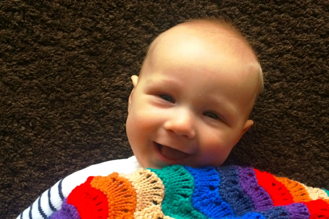 A photograph of a six month old baby boy lying underneath a rainbow blanket and smiling up at the camera Little Mister H six months update _ Mrs H's favourite things