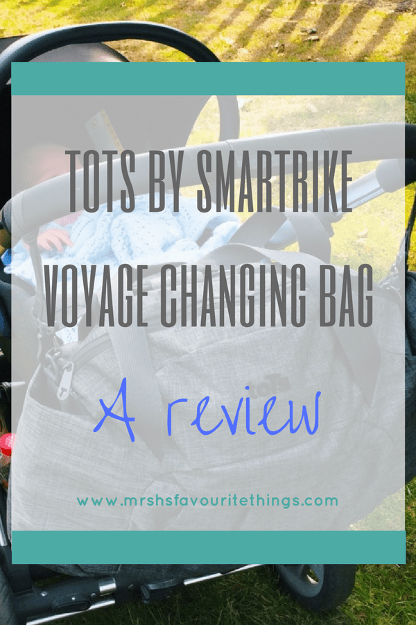 An image of the toTs by SmarTrike Dark Grey Melange Voyage Changing Bag hanging on the handle of a baby buggy with the title of the post over the top - toTs by SmarTrike Dark Grey Melange Voyage Changing Bag _ A review _ Mrs H's favourite things