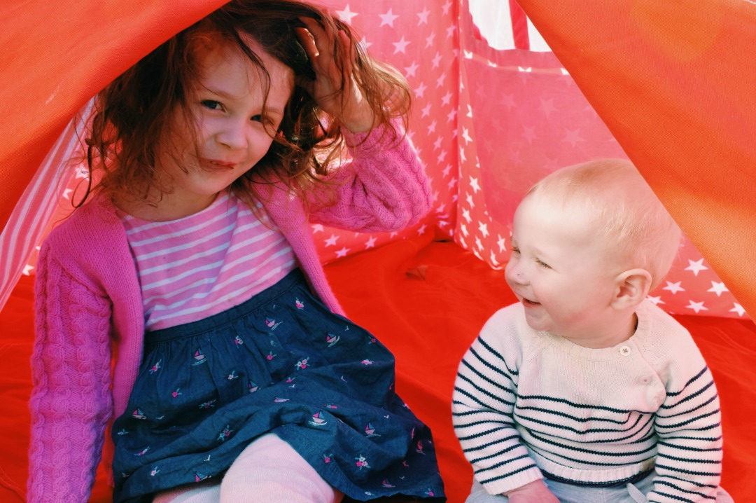 A photograph of two children, a little girl and her baby brother, sitting inside a tee pee and smiling adoringly at one another - To my children on mothers day - Mrs H's favourite things