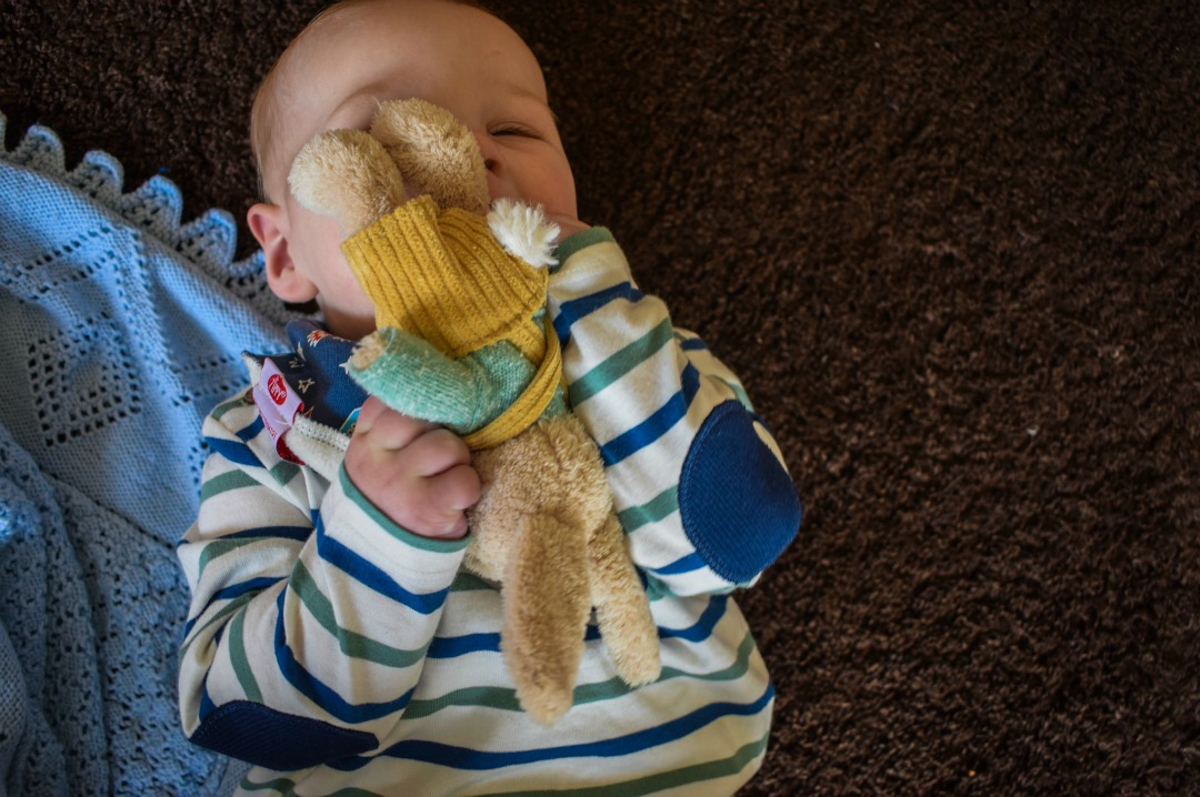 A photograph of an eight month old baby playing with some fabulous presents from the Baby section of the toy gift service website Wicked Uncle - including the A to Z Alphabet cloth book and Rabbit in Dungarees Baby Rattle from Ragtales and wearing a Fun Bandana Bib from Zippy - A Wicked Uncle Review finding the perfect baby gift _ Mrs H's favourite things