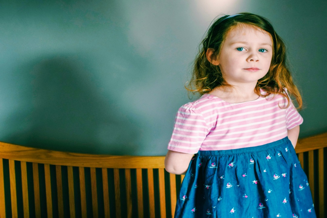 A photograph of a gorgeous three year old girl modelling some Beautiful Summer Clothes from JoJo Maman Bébé and particularly the Girls' Embroidered Chambray T-Shirt Dress - Beautiful Summer Clothes from JoJo Maman Bébé - Mrs H's favourite things