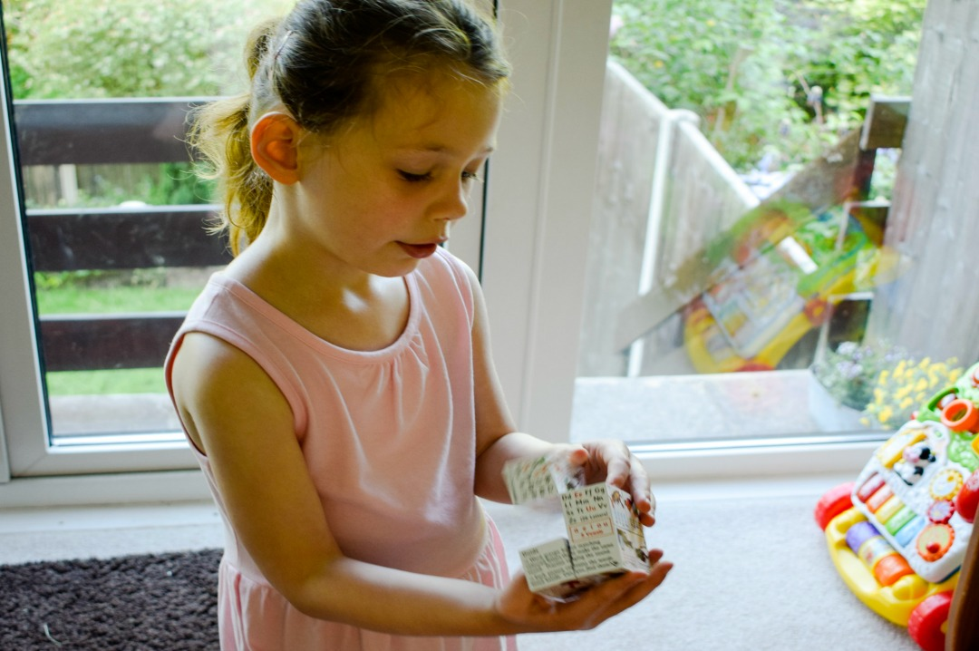 A photograph of a four year old girl playing with the fabulous educational toy the ZooBooKoo Spelling Cube Book that can be bought at Bigjigs - this is the review of that toy -which is part of our role as members of the Bigjigs Play Patrol - Mrs H's favourite things