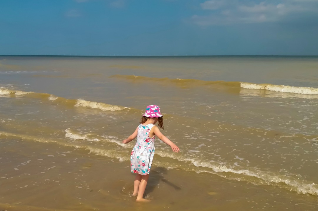 A photograph of a little girl wearing a pretty summery floral dress and sun hat paddling in the shallows of Louisa Bay, Broadstairs, Kent and looking thoughtfully out to sea - Our week in Broadstairs, Kent - Mrs H's favourite things