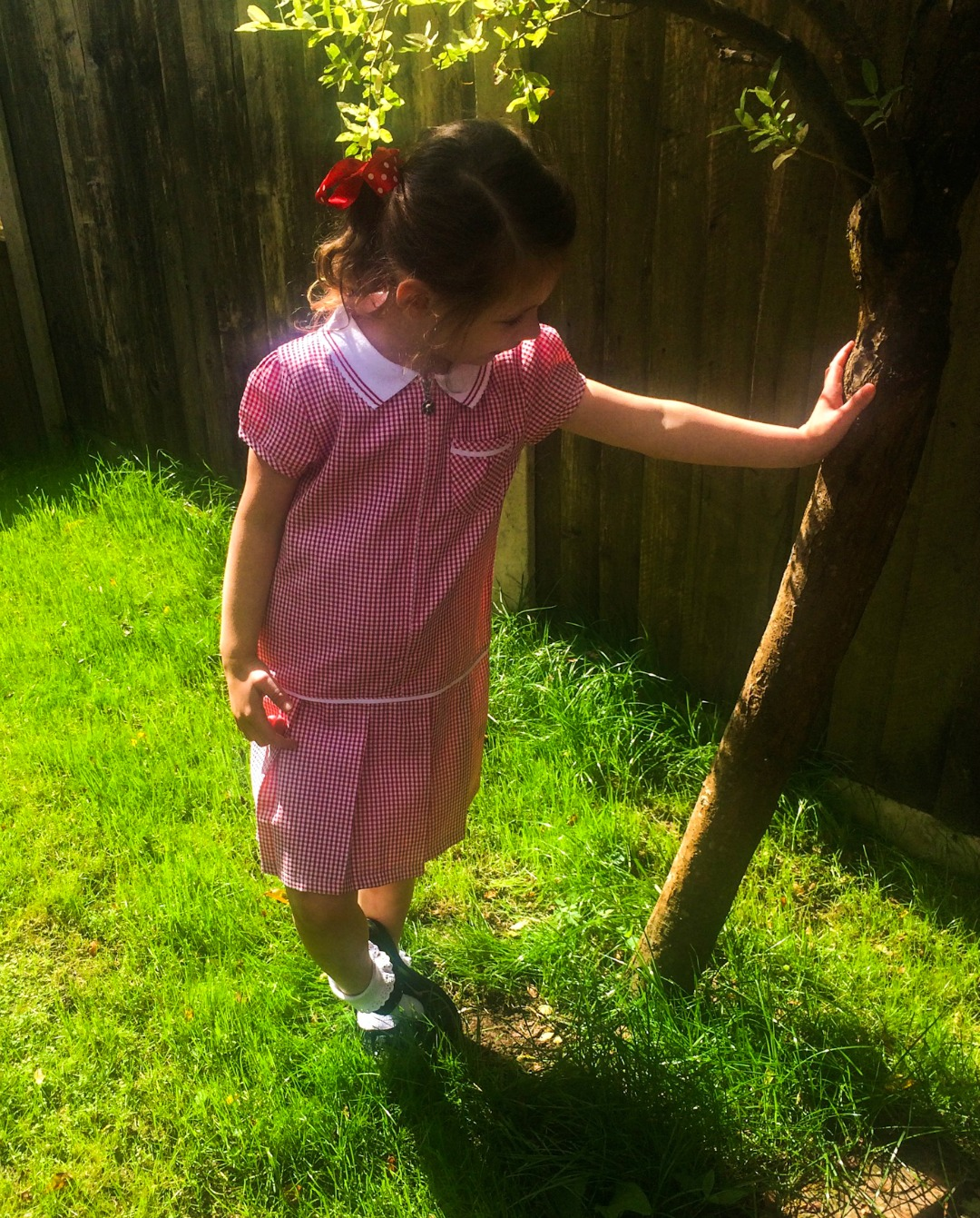 A photograph of a little girl standing in a garden and leaning against a tree - she is wearing her first school uniform and modelling her first pair of School Shoes, a pair of Lelli Kelly School Shoes - The First pair of school shoes with Jake Shoes - Mrs H's favourite things