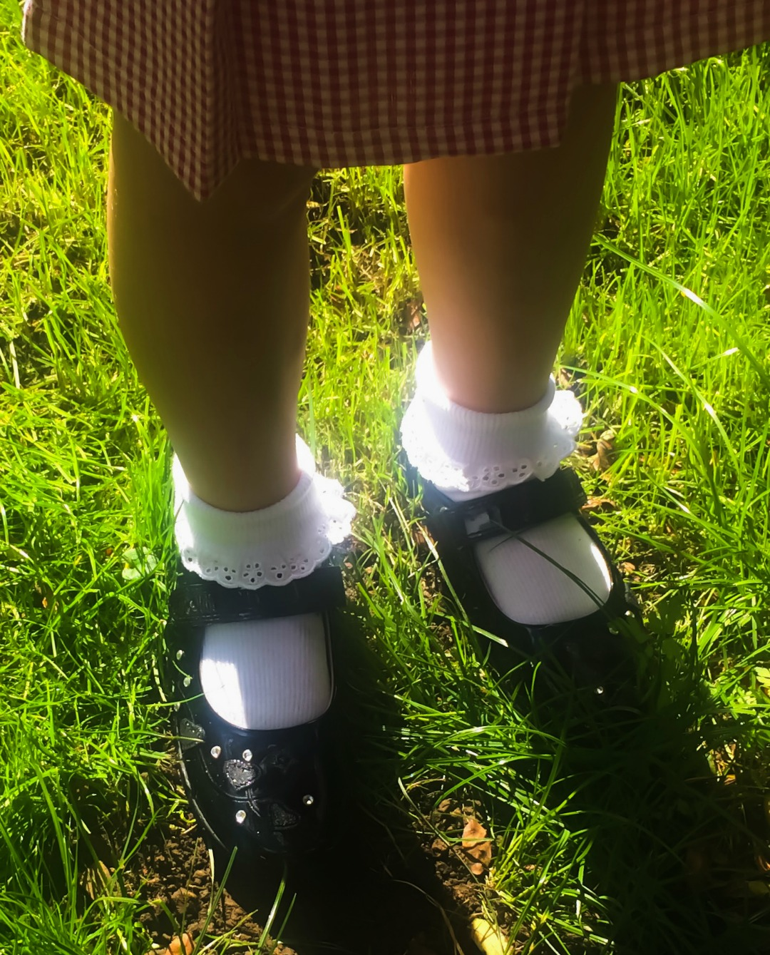 A photograph of a little girl standing in a garden and wearing her first ever pair of school shoes which are from the website Jake Shoes and a pair of black patent Lelli Kelly School Shoes - The First pair of school shoes with Jake Shoes - Mrs H's favourite things
