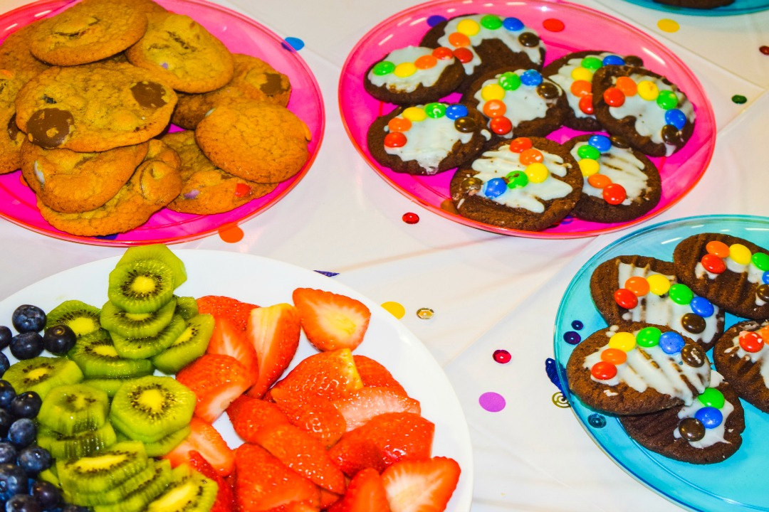 A photograph of rainbow coloured plastic plates with party food (rainbow cookies, brightly coloured fruit {kiwis and strawberries} and chocolate fork biscuits with blue icing and rainbows made from M&Ms) on a rainbow tablecloth covered in rainbow confetti - Celebrating our Rainbow Baby with Party Pieces and a Rainbow themed Welcome to the World Party - Mrs H's favourite things