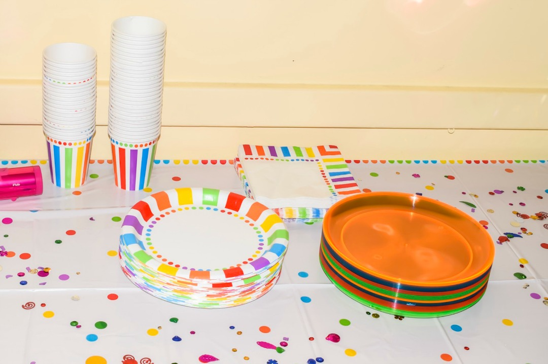 A photograph of rainbow plates, rainbow napkins, rainbow cups and plastic rainbow plates on a rainbow table cloth with rainbow confetti - all partyware is from Party Pieces and was the decoration at our rainbow themed Welcome to the World Party for our second rainbow baby, Little Mister H - Celebrating our Rainbow Baby with Party Pieces and a Rainbow Themed Welcome to the World Party - Mrs H's favourite things