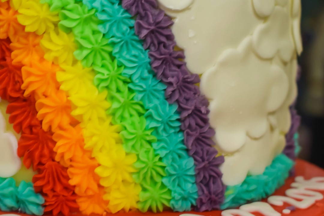 A photograph of the amazing rainbow cake that Little Sprinkles Cakery made for our son's rainbow themed Welcome to the World party - Celebrating our rainbow baby with Party Pieces and a Rainbow themed Welcome to the World party - Mrs H's favourite things