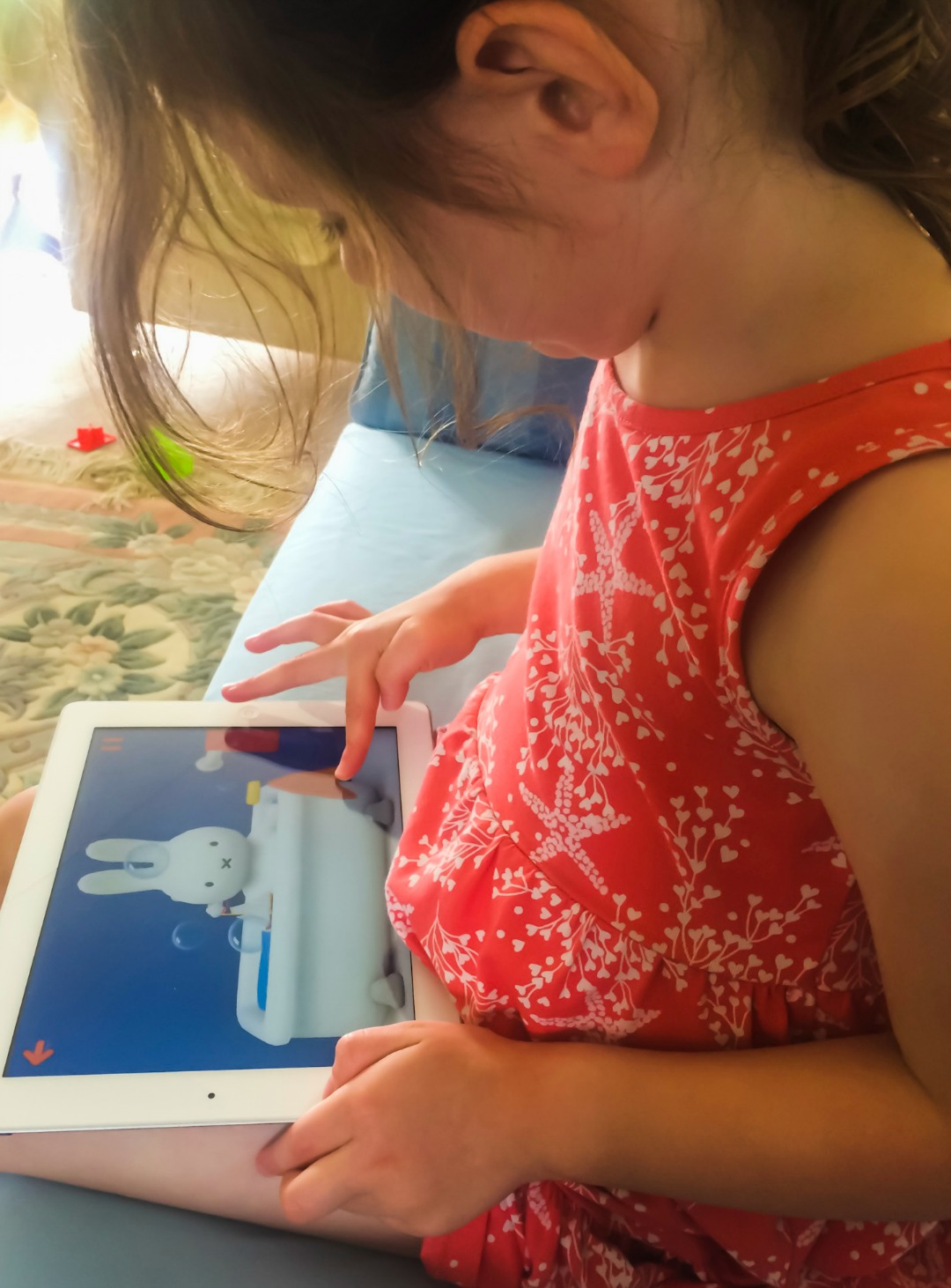 A little girl sits on a sofa and plays the Miffy World app on her mother's iPad in it Miffy is having a bath - Little Miss H in Miffy's world - Mrs H's favourite things
