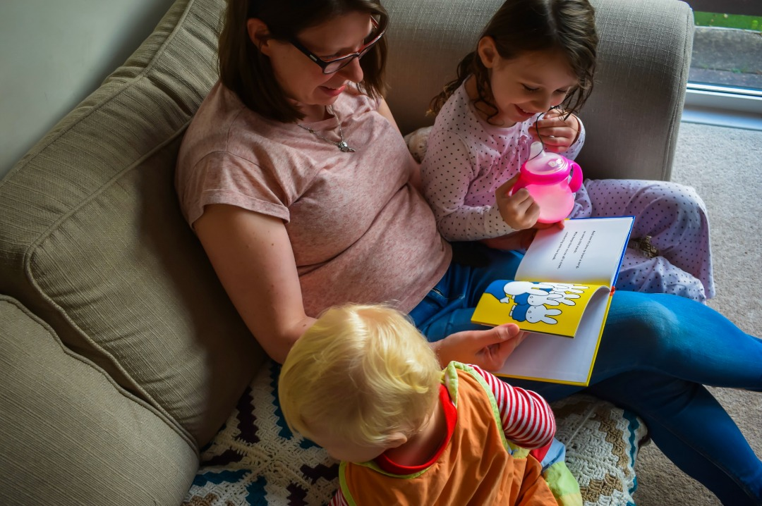 "A photograph of a mother and her son and daughter sitting on a sofa, both the children are drinking milk and are dressed in PJs ready for bed - the mother is reading the book ""Miffy at School"" by Dick Bruna as a bedtime story - Little Miss H in Miffy's World - Mrs H's favourite things"