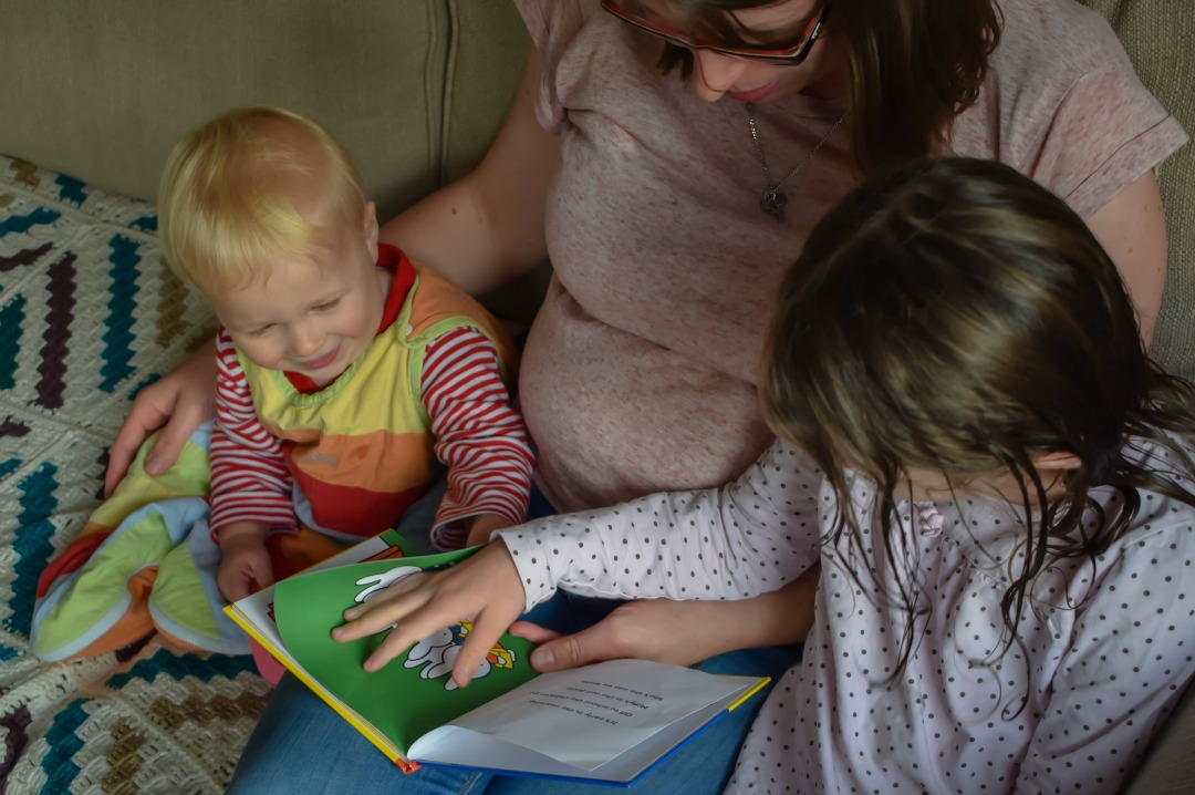 "A photograph of a mother sitting on the sofa with her son and daughter, the girl and boy are dressed in their PJs and are drinking milk, they are being read the book ""Miffy at School"" by Dick Bruna as a bedtime story - Little Miss H in Miffy's World - Mrs H's favourite things"