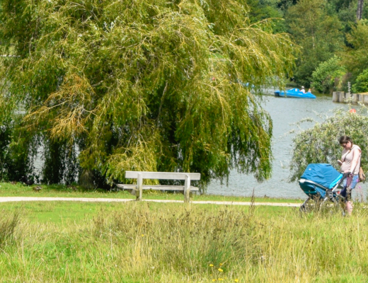 A photograph of a woman pushing her baby boy in a Diono Quantum Travel System in teal blue - she is pushing the Diono Quantum in a beautiful park (called Dunorlan Park in Tunbridge Wells) and is standing in front of the boating lake/ duck pond and there are pedalos in the background - #AdventureReady with Diono Quantum Travel System - A Review - Mrs H's favourite things