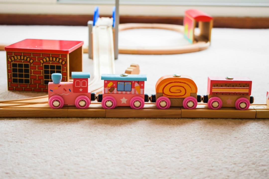 A close up photograph of the Bigjigs train the Sweetland Express set up with a generic train set on a cream carpet - Bigjigs Sweetland Express and Push-Along Rabbit - A Bigjigs Play Patrol Review - Mrs H's favourite things