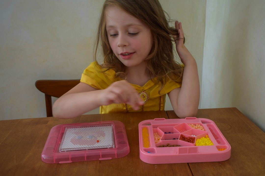 A photograph of a little girl (she is four years old) dressed in a Disney Princess Belle costume and playing with her Aquabeads Disney Princess PlaySet - Aquabeads Disney Princess Playset Review - A brilliant quiet time activity for busy kids - Mrs H's favourite things