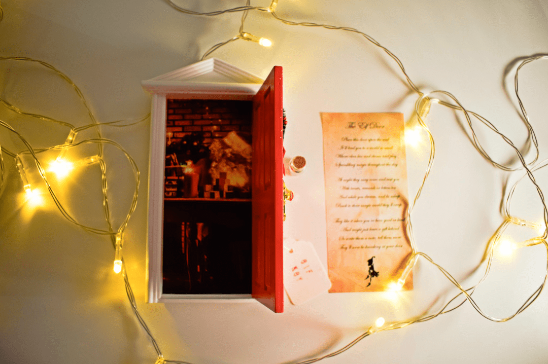 A photograph of the Opening Christmas Elf Door with Santa Claus Scene from Flitterbee - it is a beautiful miniature door painted in red and with glitter, a tiny Christmas wreath, a tiny ornate door handle and letter box - also included are a lovely poem to explain what to do with your door - some magic fairy dust - and a small elf key - surrounded by fairy lights - Flitterbee Opening Christmas Elf Door - A Review - Mrs H's favourite things