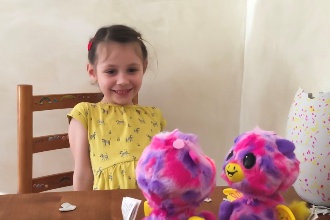 A photograph of a little girl smiling excitedly at her newly hatched Giraven twins this is the big surprise of Hatchimals surprise - TWINS - Reviewing the brand new Hatchimals: Hatchimals Surprise - Mrs H's favourite things