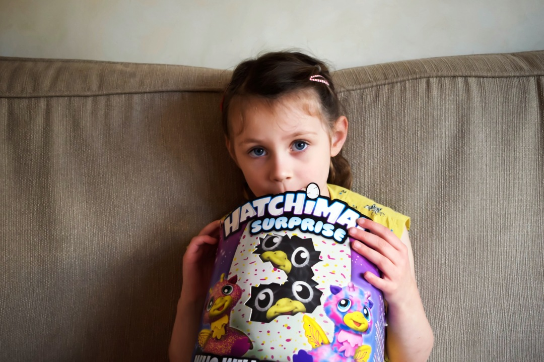 A little girl sitting on a sofa and hugging a Hatchimals Surprise box to her chest - Reviewing the Brand New Hatchimals: Hatchimals Surprise - Mrs H's favourite things