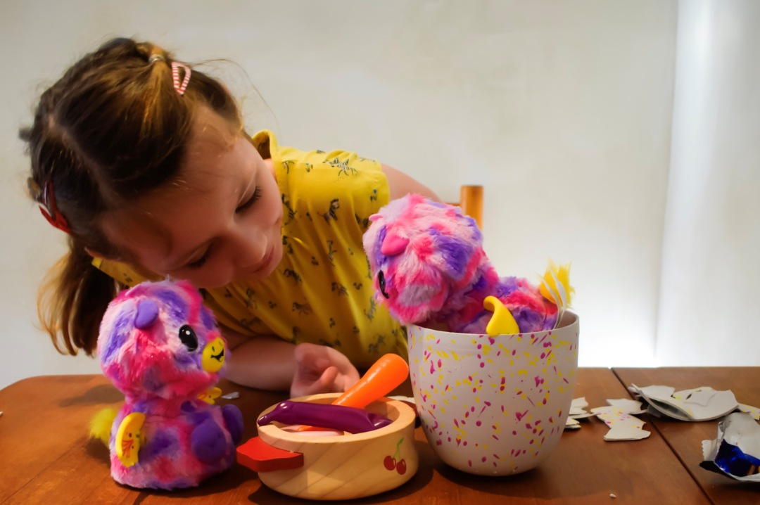 A photograph of a little girl feeding her Giraven Hatchimal twins plastic carrots and chips - Reviewing the Brand New Hatchimal: Hatchimals Surprise - Mrs H's favourite things