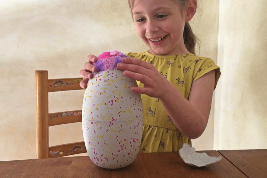 A little girl with her Hatchimals Surprise egg she is looking her excited as the egg has begun to hatch and we have the first peek of the Hatchimal inside and it has pink and purple fur - A little four year old girl with her Hatchimals Surprise egg during the hatching process - she is very excited about what the surprise is inside the Hatchimals Surprise - this photo shows the Hatchimal is almost ready to be removed from the egg and the big surprise revealed - Reviewing the brand new Hatchimals: Hatchimals Surprise - Mrs H's favourite things