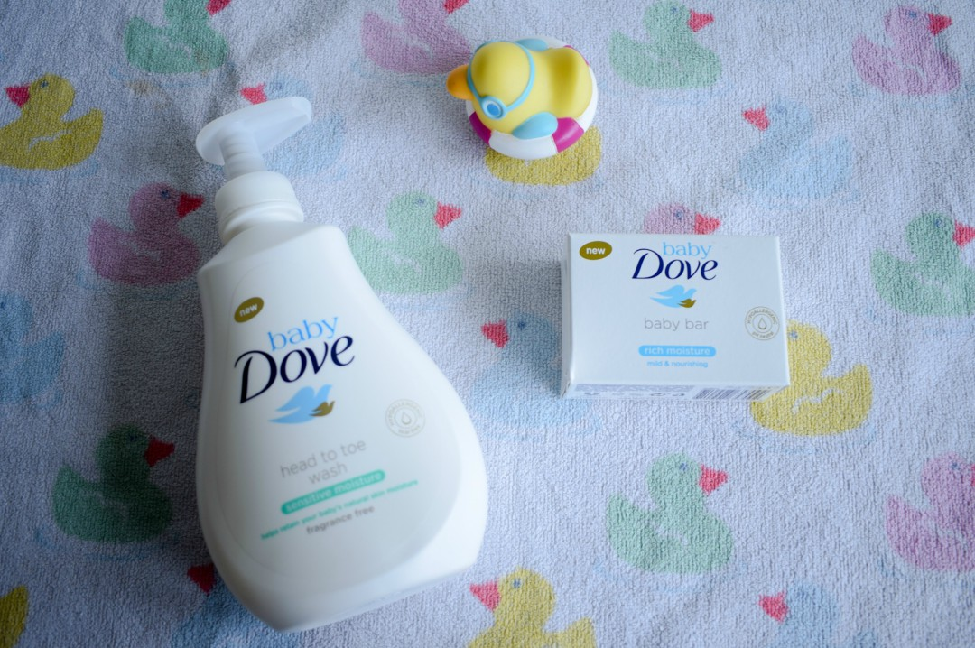 A photograph of a bottle of Sensitive Head to Toe Body Wash and Real Moisture Bar from Baby Dove lying on a towel covered in a pattern of pink, green, blue and yellow ducks and a rubber duck - Caring For My Baby My Way With Baby Dove - Mrs H's favourite things