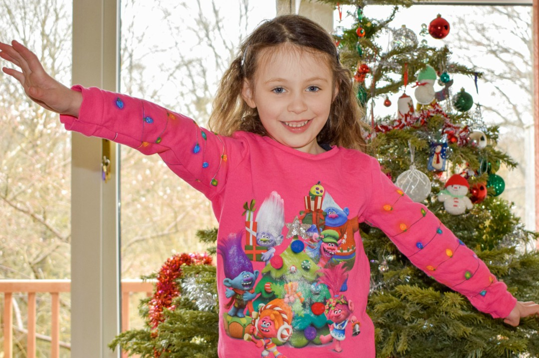 A photograph of a little girl standing in front of a Christmas tree and wearing a bright pink Trolls Christmas Sweatshirt - Having a Troll-tastic Christmas with Trolls Holiday - Mrs H's favourite things