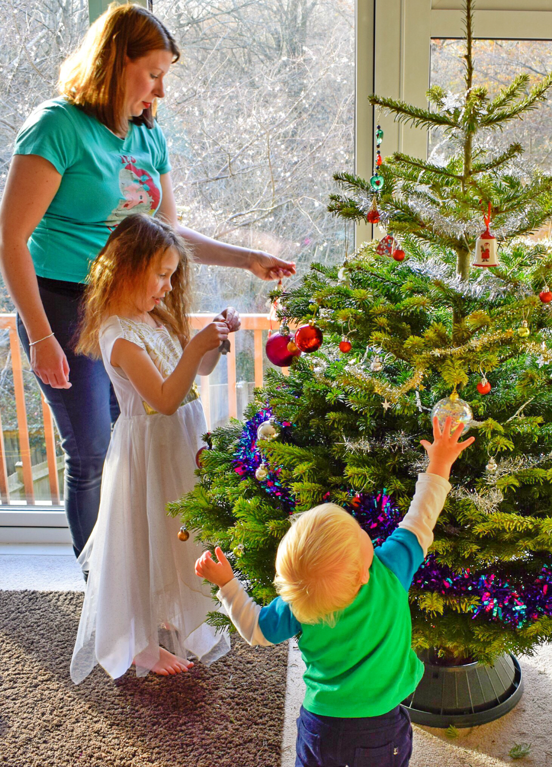 A photograph of a mum, her young daughter and her little son decorating the Christmas tree - Photographs of decorating our Christmas tree - Our Christmas Tree Day - Mrs H's favourite things