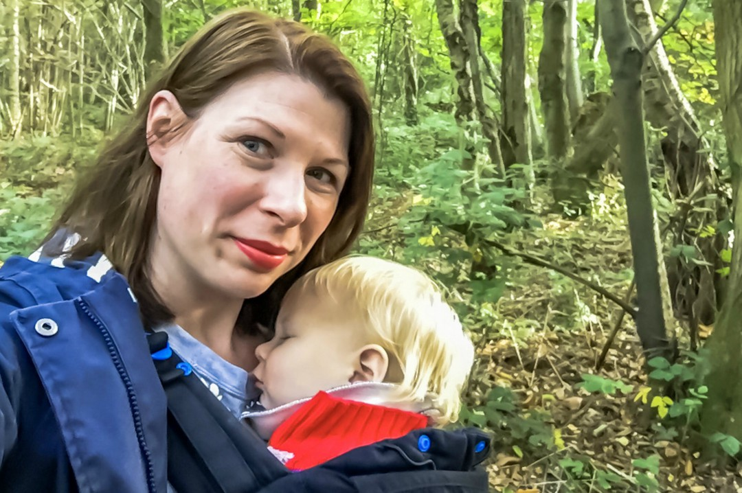 A photograph of a mother who is walking in the woods and looks happy. She is smiling at the camera and her little boy is asleep in the Pao Papoose Baby Carrier - 50 More Things That Make Me Happy - Mrs H's favourite things