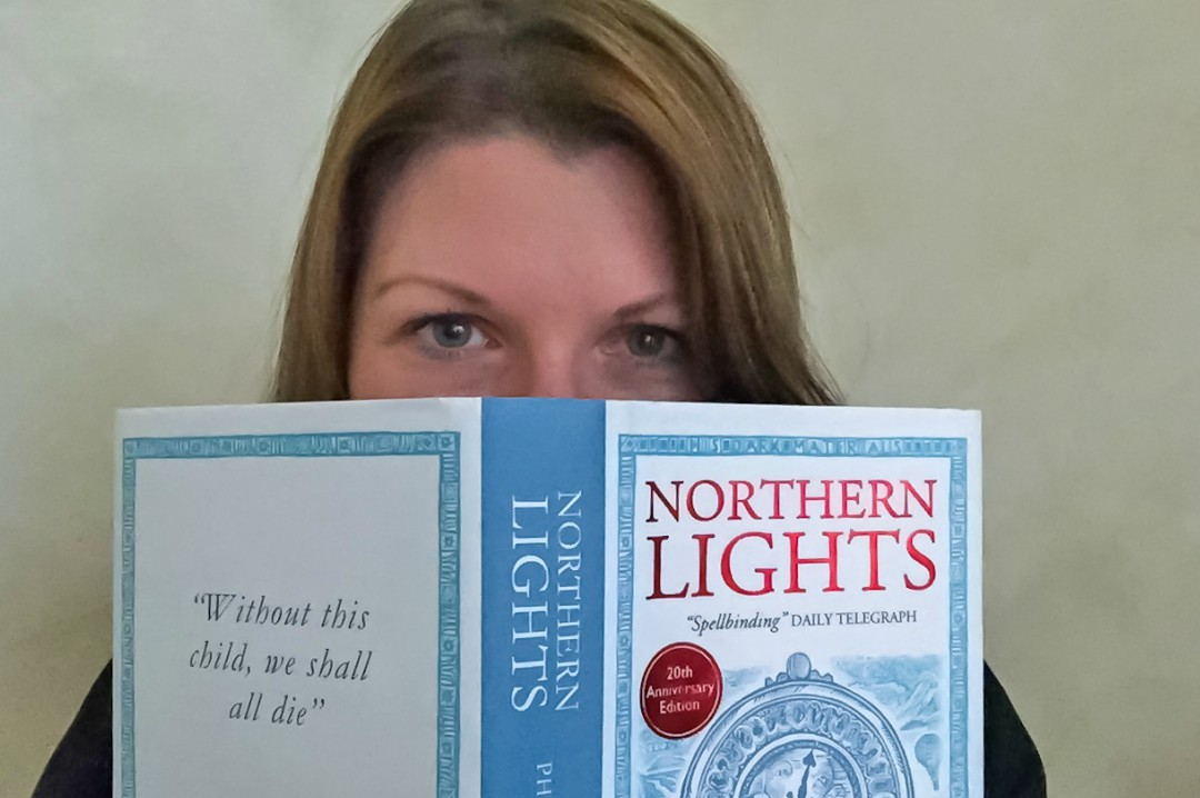 "A photograph of a brunette lady holding a hardback copy of the book ""Northern Lights"" by Philip Pullman - She is peeking over the top of the book - For the Love of Books - Mrs H's favourite things"