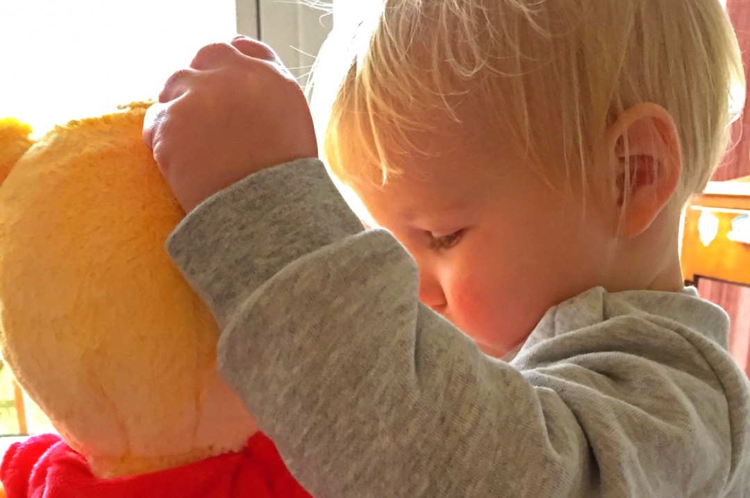 A photograph of a little boy cuddling the Snuggletime Winnie the Pooh from Posh Paws Snuggletime Winnie the Pooh Range of toys - Snuggletime Winnie the Pooh Range - A Review - Mrs H's favourite things