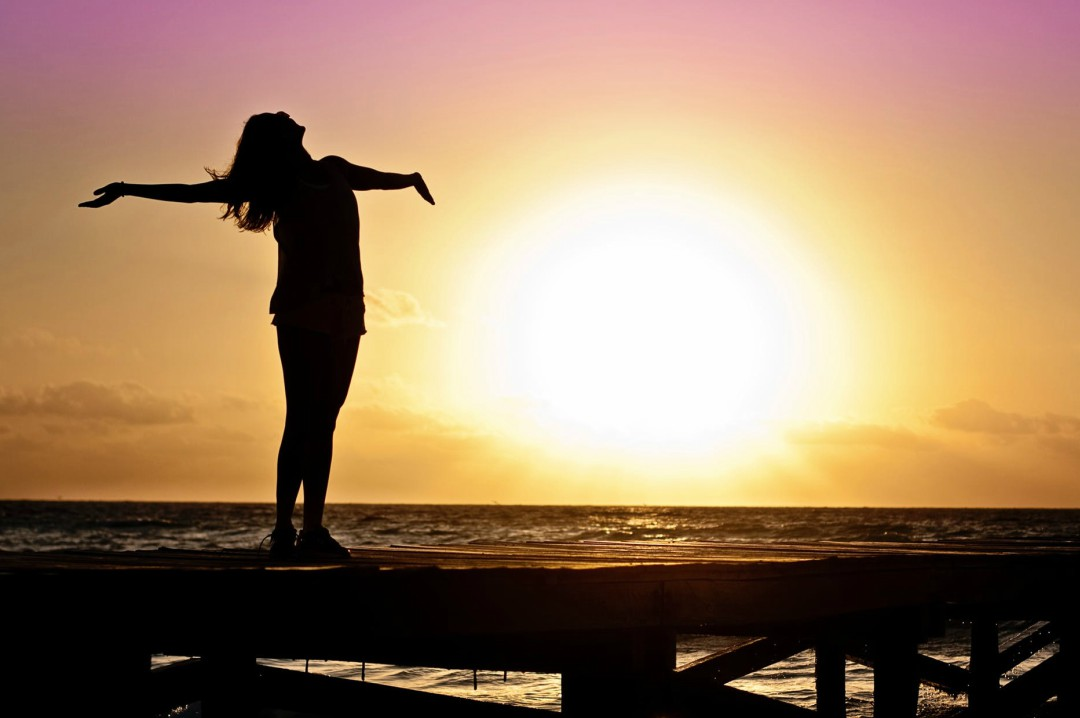 A photograph of a happy woman standing on a pier in front of a sunset - Reasons to Join The V-Gang and Become A Vegan - Mrs H's favourite things
