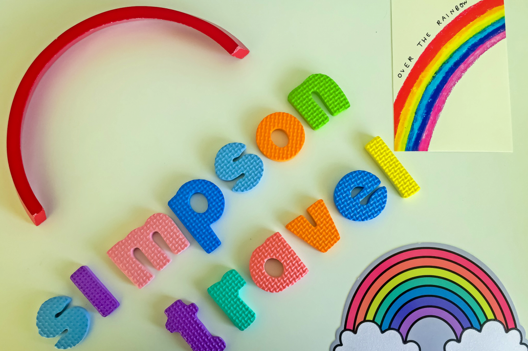 "A photograph of a wooden rainbow toy (showing only the red arc of the rainbow), two postcards of rainbows and foam letters spelling out ""Simpson Travel"" - Chasing Rainbows with Simpson Travel - Mrs H's favourite things"