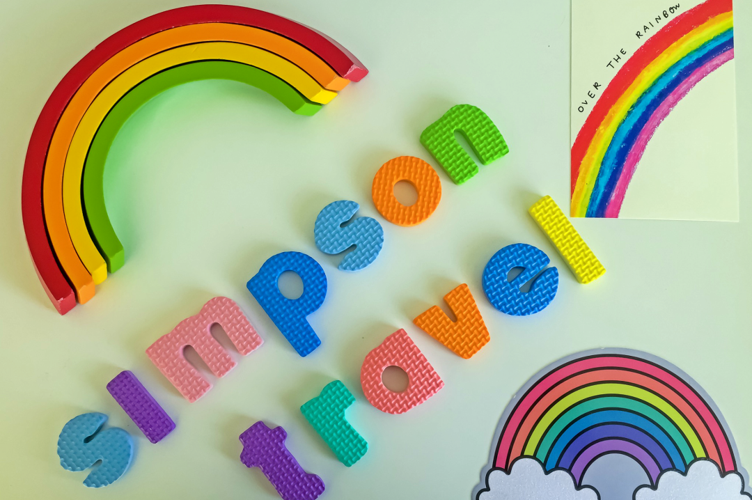 "A photograph of a wooden rainbow toy (showing only the red, orange yellow and green arc of the rainbow), two postcards of rainbows and foam letters spelling out ""Simpson Travel"" - Chasing Rainbows with Simpson Travel - Mrs H's favourite things"