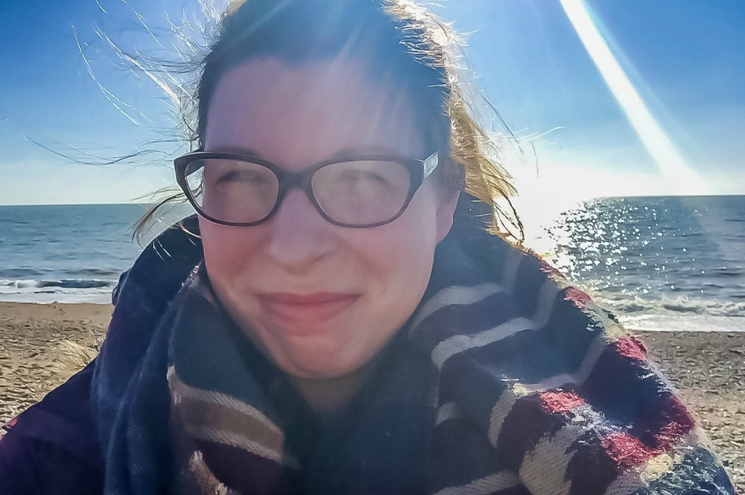 A photograph of a woman at the beach with a sun glare across the photo - Could Decluttering Help Your Mindset? How To Get Started - Mrs H's favourite things