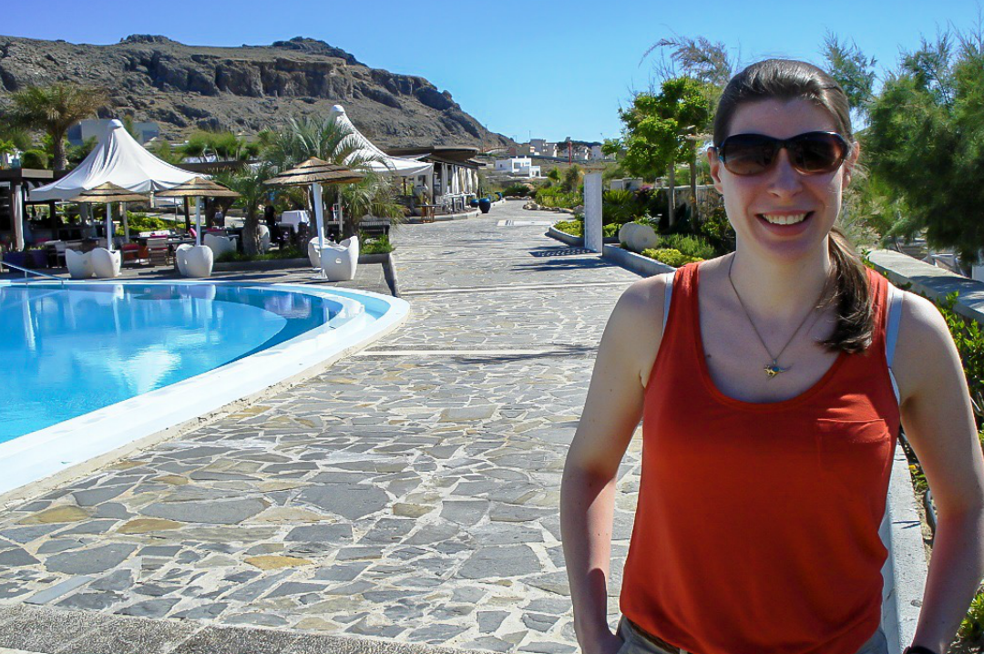 A photograph of a happy and healthy woman standing in front of a swimming pool in a hotel in Rhodes - Tools For Improving Your Health - Mrs H's favourite things
