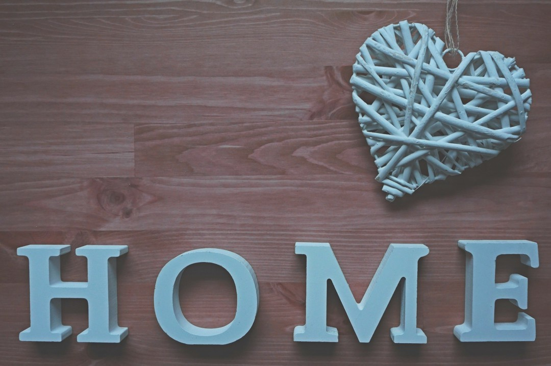 A photograph of a sign saying home and a wicker heart on a wooden table - How To Feel Better Within The Walls Of Your Own Home - Mrs H's favourite things