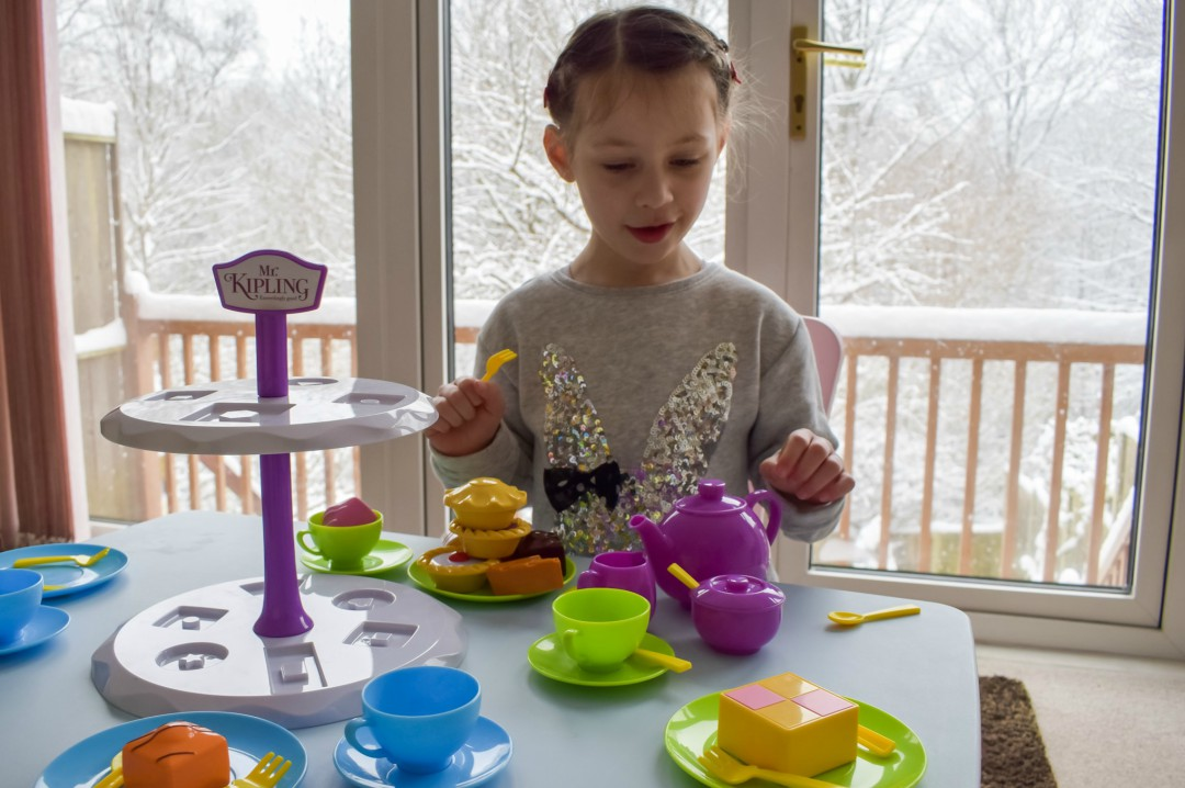 A photograph of a little girl playing imaginatively with the Casdon Mr Kipling Tea Set and Cake Stand - Imaginative Play with the Casdon Mr Kipling Tea Set - A Review - Mrs H's favourite things