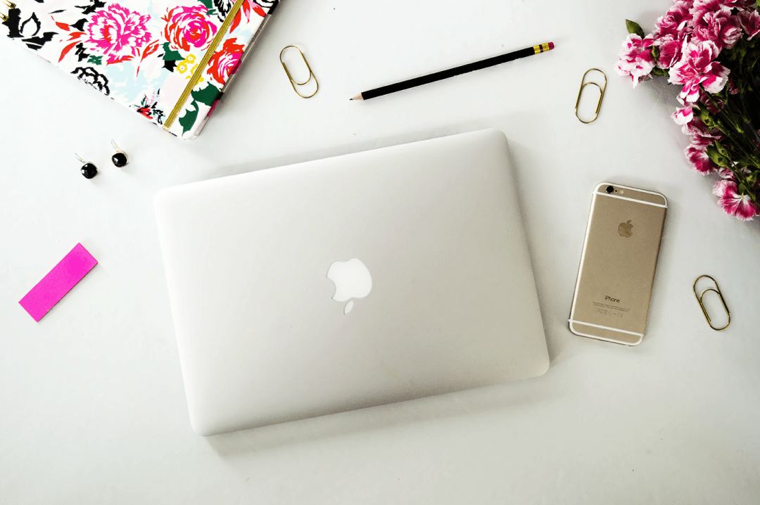 A stock image photograph of a white Mac on a white desk, surrounded by a flowery notebook, some pink peonies, some rose gold paperclips, a pencil and a rose gold iPhone - How To Turn Blogging Into A Career - Mrs H's favourite things