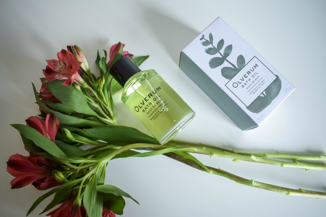 A photograph of a bottle of Olverum Bath Oil and the box it came in with a bunch of flowers - Mothers Day Gift List - Treats for the Mother in your Life - Mrs H's favourite things