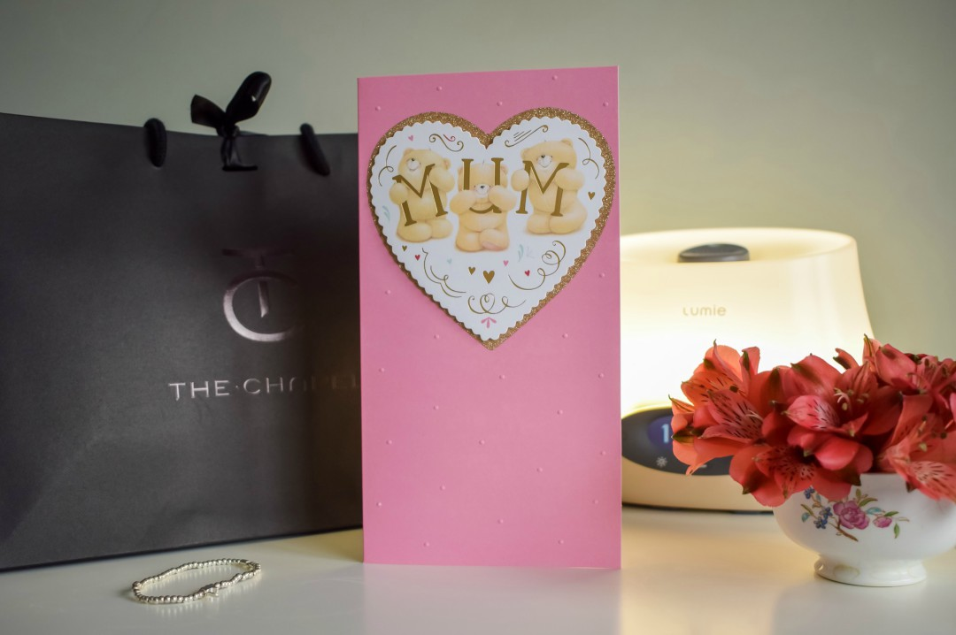 A photograph of a Mother's Day card saying Mum from Hallmark, a gift bag from The Chapel, a silver bracelet, a Lumie Iris Bodyclock and some flowers in a tea cup - Mother's Day Gift List - Treats for the Mother in your Life - Mrs H's favourite things