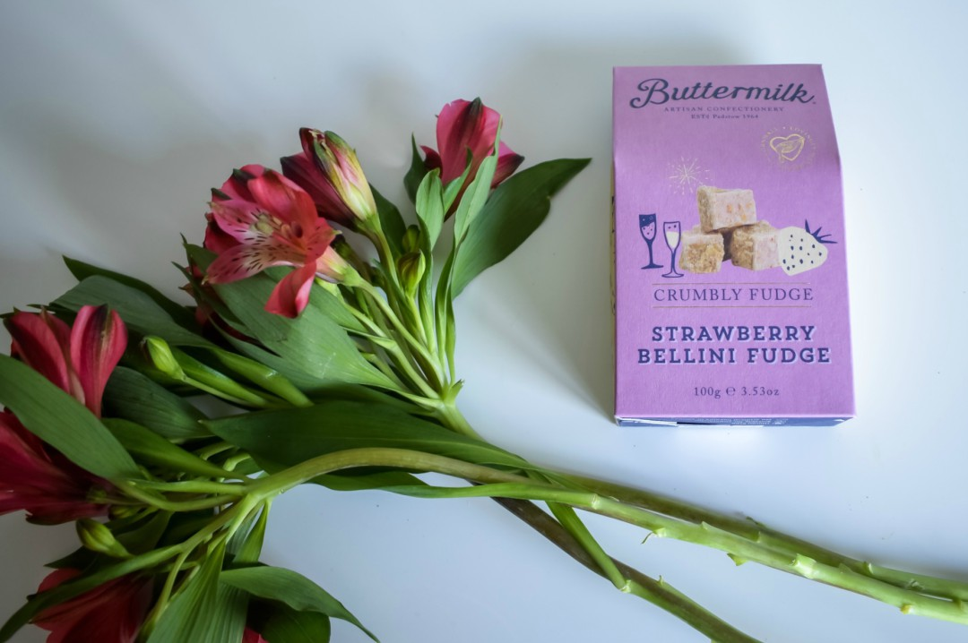A photograph of a box of Strawberry bellini fudge from Buttermilk with a bunch of flowers next to it - Mother's Day Gift List - Treats for the Mother in your Life - Mrs H's favourite things