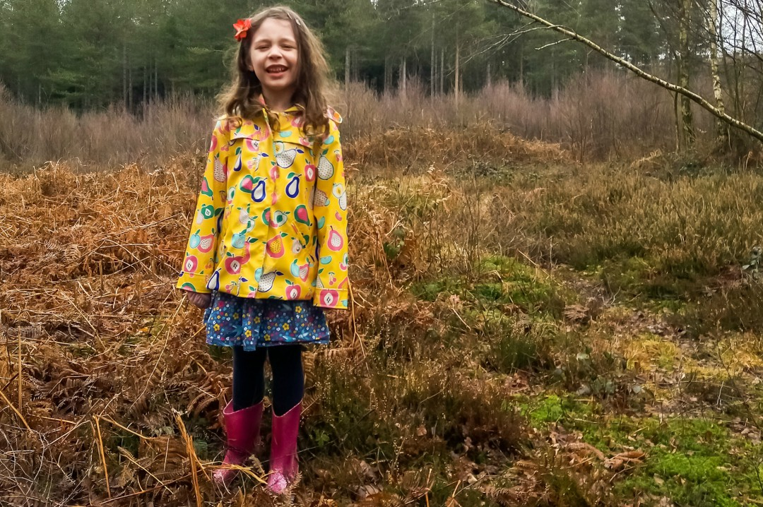 A photograph of a little girl wearing a yellow mac and pink sparkly wellies and standing in a wood - Our Weekend Happy #9 - Seeing Grandparents, A Lie In & A Lovely Mother's Day Lunch - Mrs H's favourite things