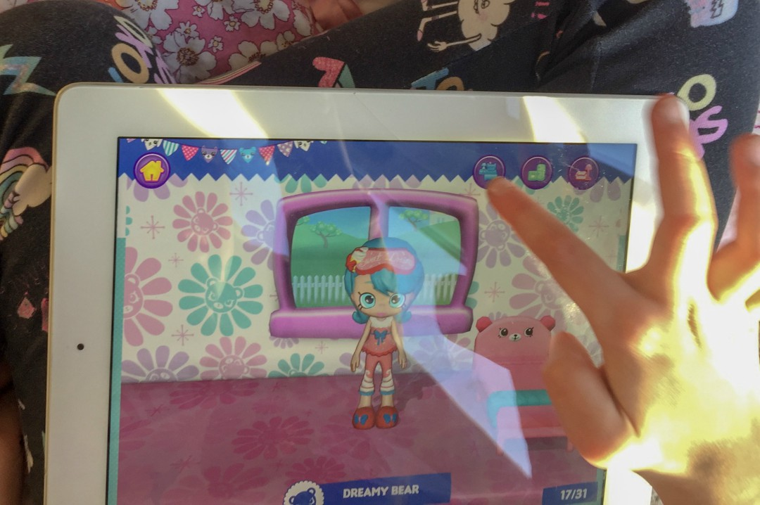 A photograph of a little girl playing the Shopkins Happy Places App by Kuato Studios and Moose Toys - A Shopkins Happy Places App - A Review - Mrs H's favourite things