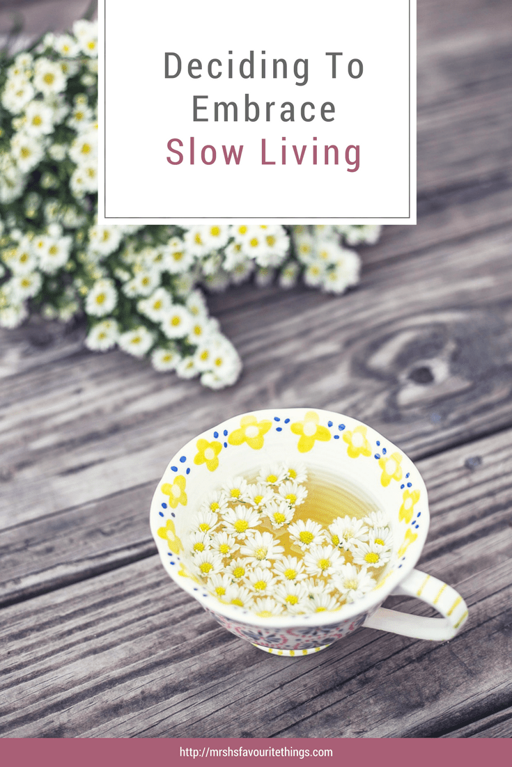 A Pinterest Graphic photograph of a cup of camomile tea and a bunch of daisies with the text Deciding to Embrace Slow Living - Deciding To Embrace Slow Living - Mrs H's favourite things