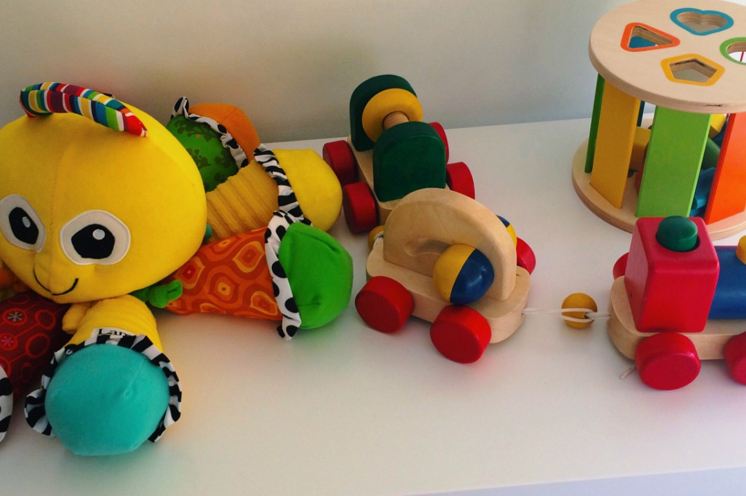 A photograph of some brightly coloured toys on top of a white storage unit in a kid's bedroom - Decorating Your Kid's Bedroom - The Key Considerations - Mrs H's favourite things