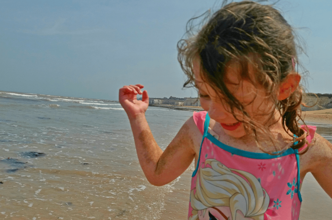 A photograph of a little girl on a sandy beach on a sunny day - The Importance Of Having A Family Holiday To Look Forward To - Mrs H's favourite things -